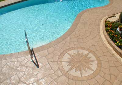 Pool deck with compass design in stamped concrete.